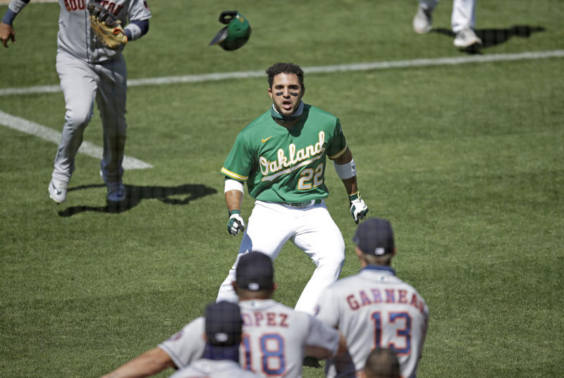 Ramón Laureano on the field in an Oakland jersey. Astros players backs are in the forefront of the photo.