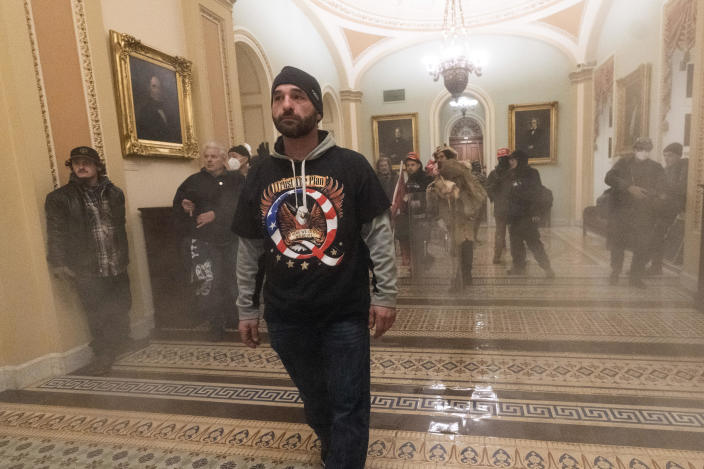 Smoke fills the walkway outside the Senate Chamber as members of a pro-Trump mob are confronted by U.S. Capitol Police officers during the riot on Jan. 6, 2020. The man in the QAnon t-shirt, who was seen on video chasing a Black officer in the Capitol, has been identified as Doug Jensen of Iowa, who has been arrested and faces multiple charges. / Credit: Manuel Balce Ceneta / AP