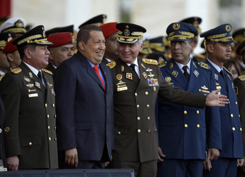 FILE - In this Jan. 17, 2012 file photo, Venezuela's Defense Minister Gen. Henry Rangel Silva, left, President Hugo Chavez, second from left, and outgoing Defense Minister Gen. Carlos Mata Figueroa, third from left, attend Rangel Silva's swearing-in ceremony at the Fort Tiuna military base in Caracas, Venezuela. The shadow of the Venezuelan military hangs over Sunday's presidential election, with many people wondering how the armed forces might react if Chavez stumbles in his fight to stay in power.(AP Photo/Fernando Llano, File)