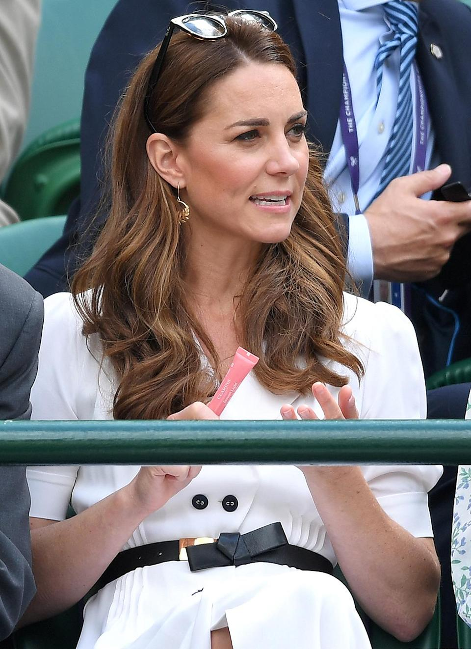 """<p>Kate pulled out this lip gloss from her purse at Wimbledon 2019 to keep her makeup fresh, even in the summer sun.</p> <p><strong>Buy It! Clarins Instant Light Natural Lip Perfector, <a href=""""https://www.amazon.com/Clarins-Instant-Light-Natural-Perfector/dp/B00274Z6HO/?ots=1&tag=people0d0-20&linkCode=w50"""" rel=""""sponsored noopener"""" target=""""_blank"""" data-ylk=""""slk:$25"""" class=""""link rapid-noclick-resp"""">$25</a></strong></p> <p><strong>Get the Look!<br></strong><strong>Nars Lip Gloss, <a href=""""https://www.pntrac.com/t/8-10989-131940-141079?sid=PEO18RegalMothersDayGiftsInspiredbyRealLifeRoyalMomspetitsRoyGal12686606202105I