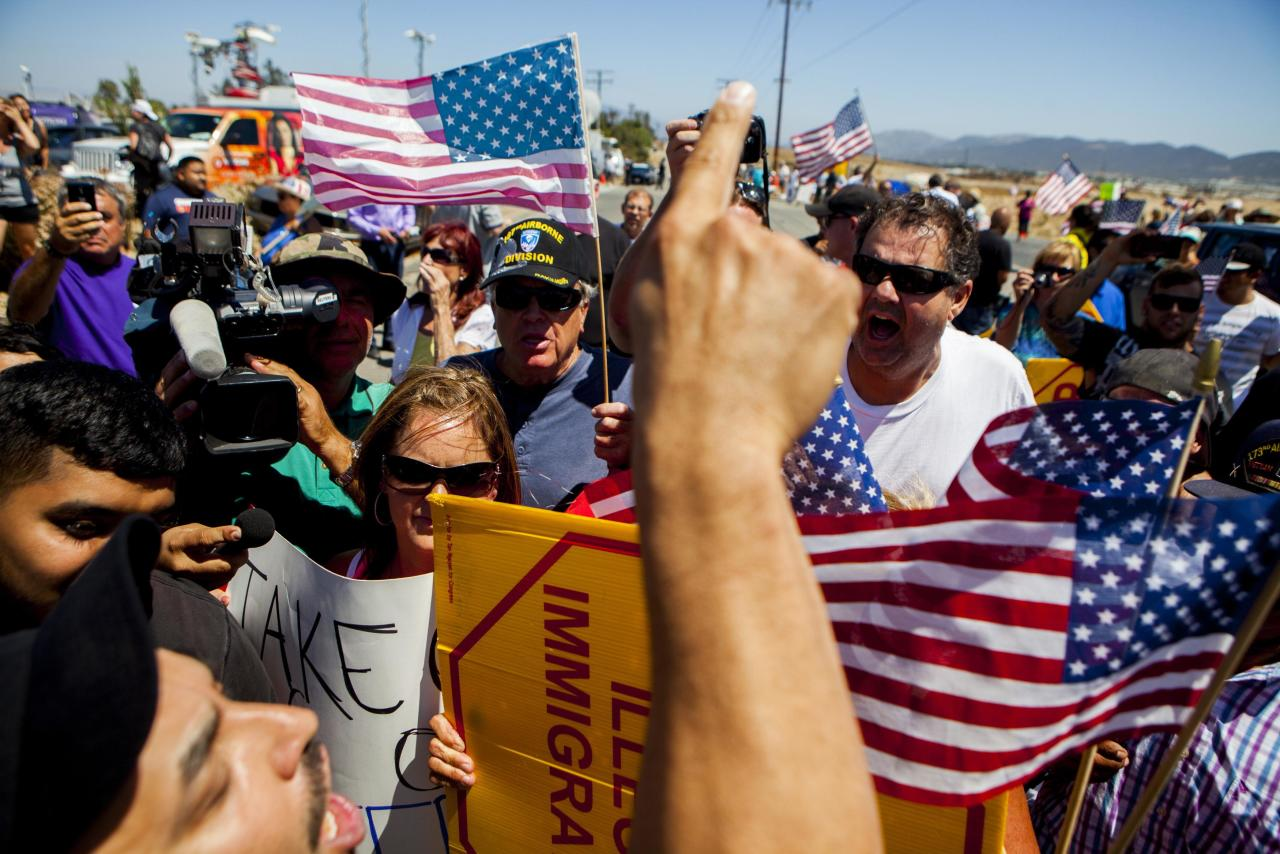 Demonstrators picketing against the arrival of undocumented migrants who were scheduled to be processed at the Murrieta Border Patrol Station block the buses carrying the migrants in Murrieta, California July 1, 2014. Some 140 undocumented immigrants, many of them women with children, will be flown from Texas to California and processed through a San Diego-area U.S. Border Patrol station as federal officials deal with a crush of Central American migrants at the border, a local mayor said on Monday. REUTERS/Sam Hodgson (UNITED STATES - Tags: SOCIETY IMMIGRATION CIVIL UNREST)
