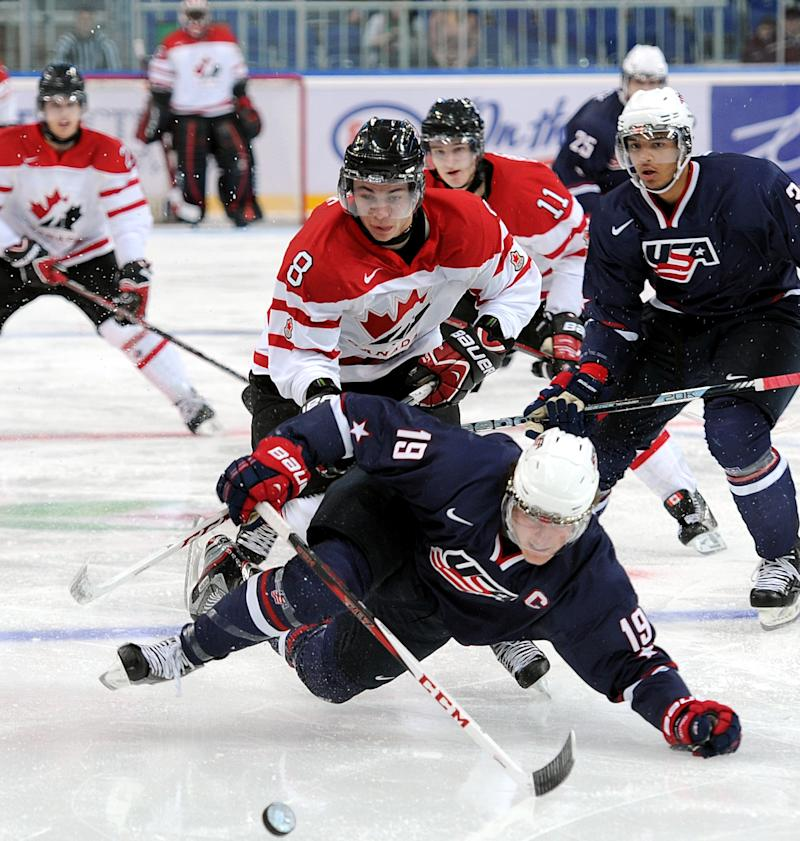 USA's Jake McCabe, centre,  falls with Canada's Ty Rattie, # 8, following him during their semi-final match at the the World Junior Ice Hockey championship in Ufa, Russia, Thursday, Jan. 3, 2013. (AP Photo/Yuri Kuzmin, KHL)