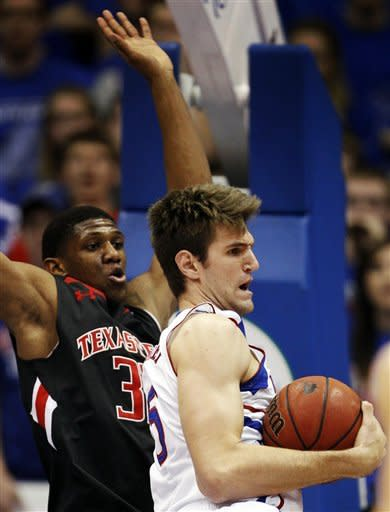 Kansas center Jeff Withey (5) pulls in a rebound against Texas Tech forward Jordan Tolbert (32) during the first half of an NCAA college basketball game in Lawrence, Kan., Saturday, Feb. 18, 2012. (AP Photo/Orlin Wagner)