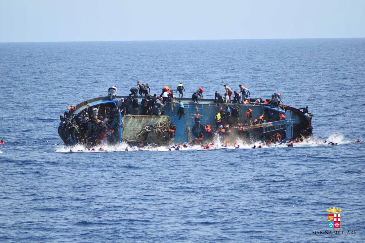 "Migrants are seen on a capsizing boat before a rescue operation by Italian navy ships ""Bettica"" and ""Bergamini"" off the coast of Libya in this handout picture released by the Italian Marina Militare on May 25, 2016. Marina Militare/Handout via REUTERS    ATTENTION EDITORS - THIS PICTURE WAS PROVIDED BY A THIRD PARTY. FOR EDITORIAL USE ONLY."