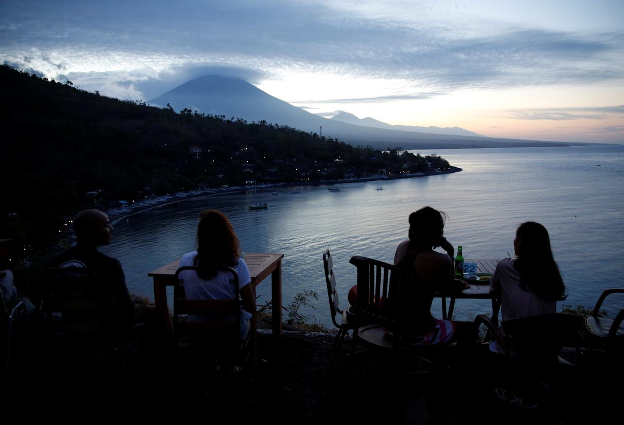 <p>Tourists have a drink while watching the sunset behind Mount Agung, a volcano on the highest alert level, in Amed on the resort island of Bali, Indonesia on Sept. 25, 2017. (Photo: Darren Whiteside/Reuters) </p>