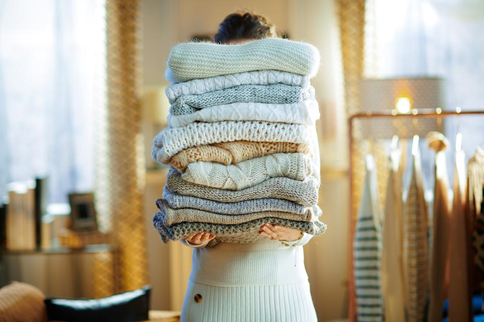 woman in white sweater and skirt in house in sunny winter day holding huge pile of sweaters.