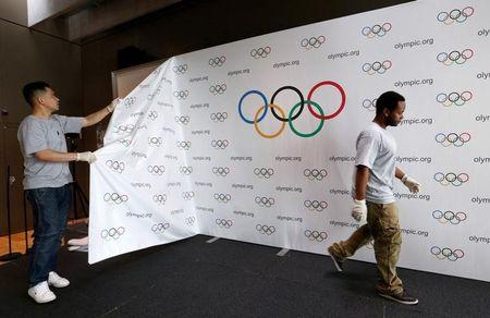 Staff of the IOC dismantle a backdrop after a news conference after the Olympic Summit on doping in Lausanne
