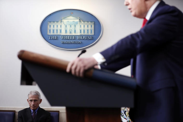 FILE - In this April 9, 2020, file photo Dr. Anthony Fauci, director of the National Institute of Allergy and Infectious Diseases, listens as President Donald Trump speaks about the coronavirus in the James Brady Press Briefing Room of the White House in Washington. (AP Photo/Andrew Harnik, File)