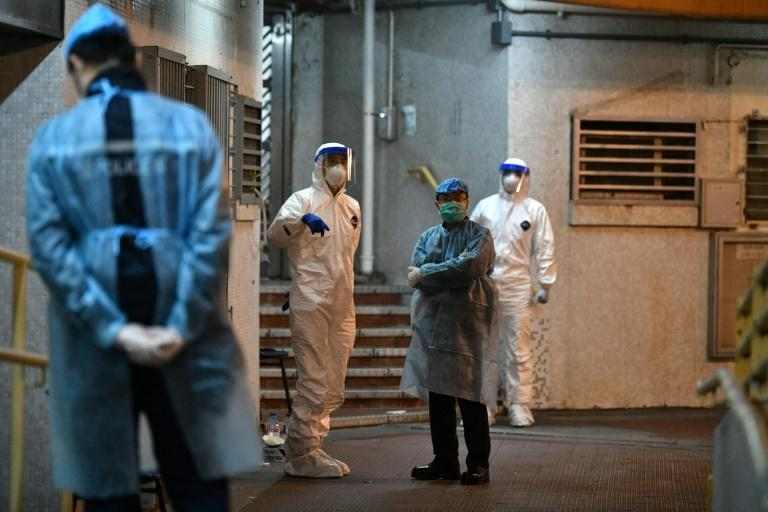Medical personnel wearing protective suits wait at a residential estate in Hong Kong after two people in the block were confirmed to have contracted the coronavirus