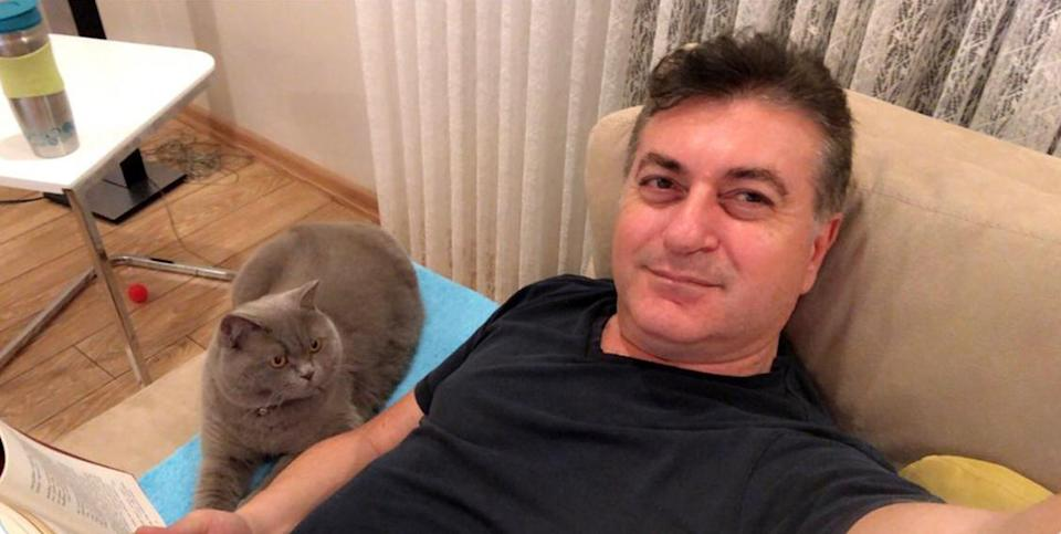 Real estate agent Mustafa Murat Ayhan, 48, is pictured with a cat.