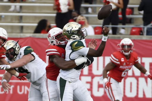 South Florida quarterback Katravis Marsh, right, fumbles while being sacked by Houston defensive lineman David Anenih during the second half of an NCAA college football game, Saturday, Nov. 14, 2020, in Houston. (AP Photo/Eric Christian Smith)