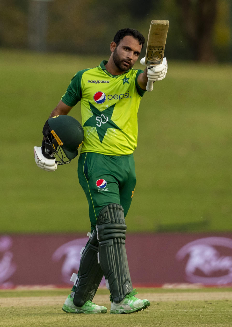Pakistan's batsman Fakhar Zaman raises his bat to celebrate scoring a half century during the fourth and final T20 cricket match between South Africa and Pakistan at Centurion Park in Pretoria, South Africa, Friday, April 16, 2021. (AP Photo/Themba Hadebe)