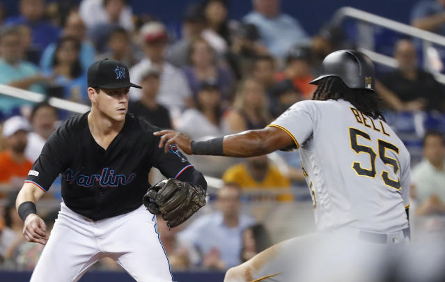 Miami Marlins third baseman Brian Anderson, left, prepares to tag out Pittsburgh Pirates' Josh Bell (55), who was trying to advance from second on a grounder by Colin Moran during the fourth inning of a baseball game Saturday, June 15, 2019, in Miami. (AP Photo/Wilfredo Lee)