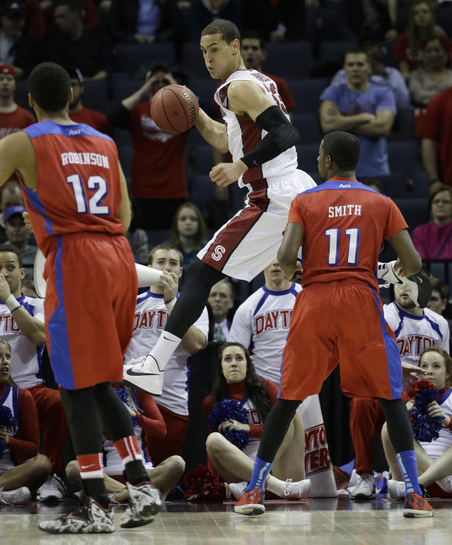 Stanford forward Dwight Powell (33) works on a save as Dayton forward/center Jalen Robinson (12) and Dayton guard Scoochie Smith (11) look on during the first half in a regional semifinal game at the NCAA college basketball tournament, Thursday, March 27, 2014, in Memphis, Tenn. (AP Photo/Mark Humphrey)