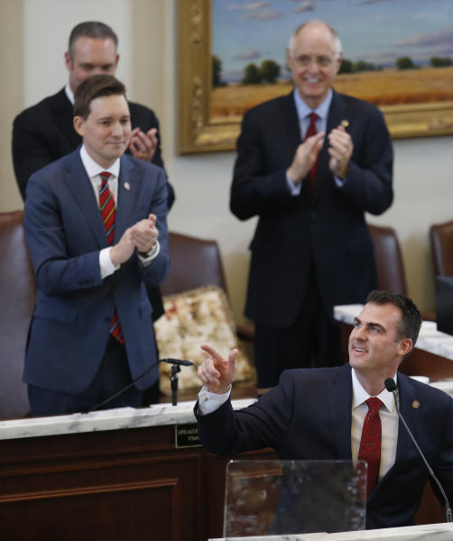 Oklahoma Gov. Kevin Stitt, right, gestures as he is applauded by Lt. Gov. Matt Pinnell, left, and others during his State of the State address in Oklahoma City, Monday, Feb. 4, 2019. (AP Photo/Sue Ogrocki)