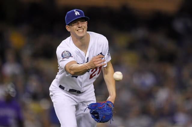 Los Angeles Dodgers starting pitcher Walker Buehler winces as he throws out Colorado Rockies' Trevor Story after being hit by the batted ball during the fifth inning of a baseball game Monday, May 21, 2018, in Los Angeles. (AP Photo/Mark J. Terrill)