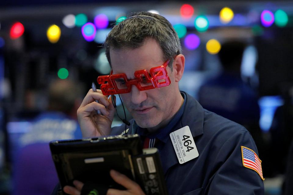 Trader Gregory Rowe works on the trading floor as the final day of trading for the year draws to a close with the Dow Jones Industrial Average setting a record high close for a trading year at the New York Stock Exchange (NYSE) in Manhattan, New York, U.S., December 29, 2017. REUTERS/Andrew Kelly