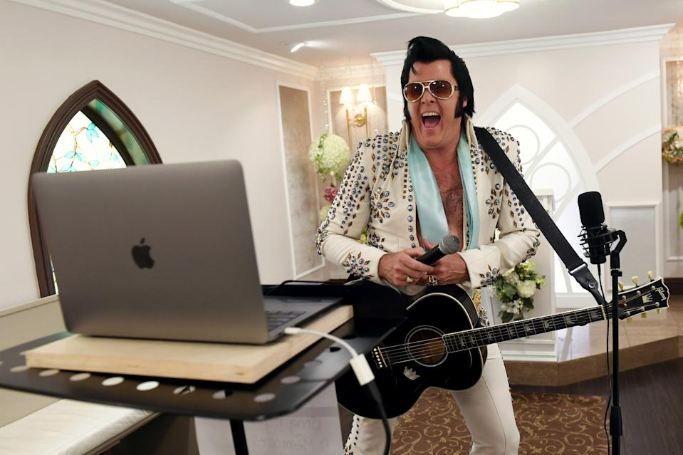 Elvis Presley impersonator and chapel co-owner Brendan Paul performs a live wedding vow renewal ceremony using the Zoom videoconferencing software for a couple from Texas celebrating their 50th anniversary amid the spread of the COVID-19 at Graceland Wedding Chapel on July 28, 2020, in Las Vegas, Nevada. (Photo by Ethan Miller/Getty Images)