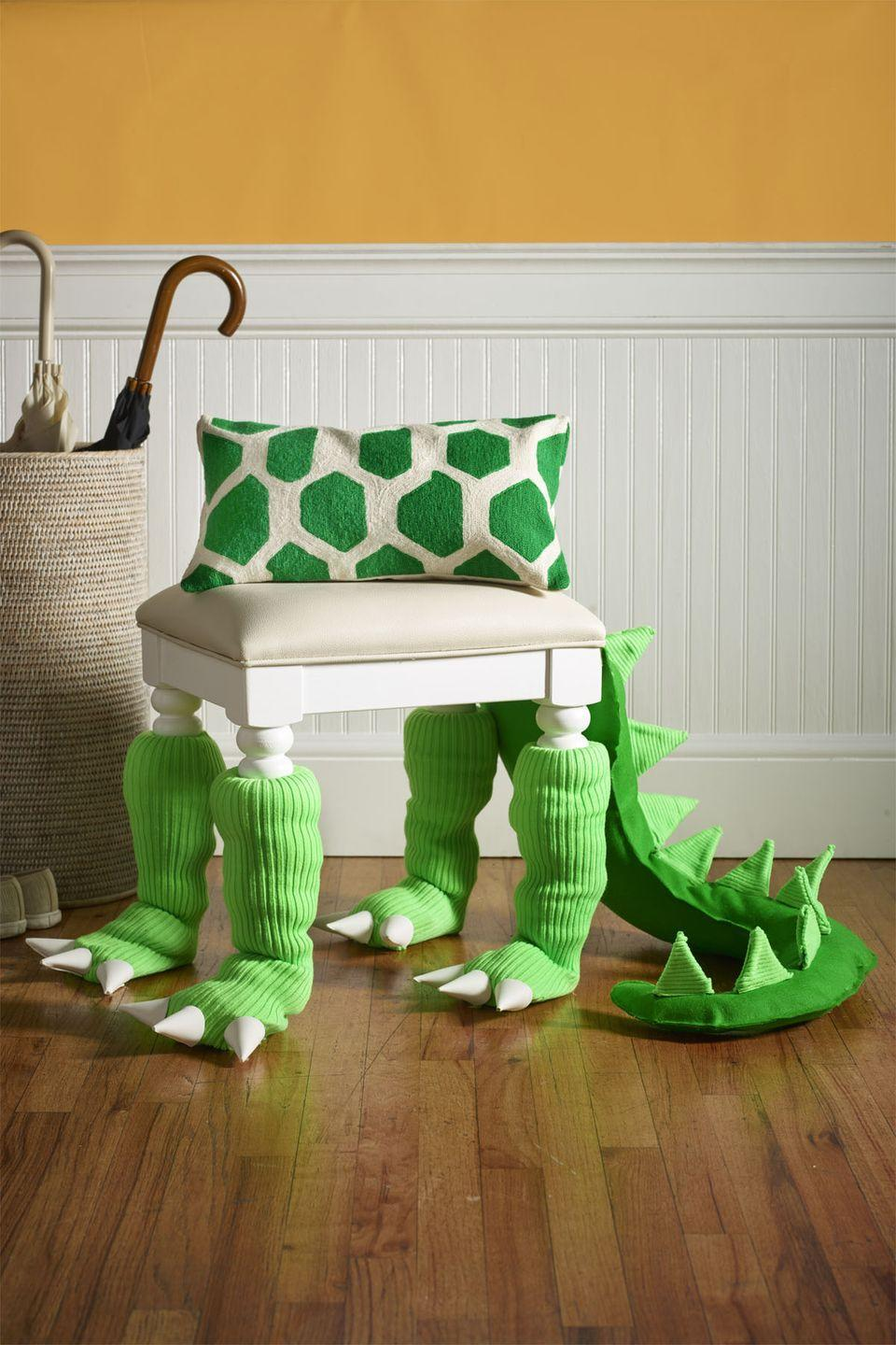 """<p>Green leg warmers are a fun and easy way to add Halloween flair to your entryway bench.</p><p><strong>1. </strong>Tape pillow batting around bench legs, then slip on leg warmers and leave <span>6</span>"""" of fabric at bottom for feet.</p><p><strong>2. </strong>Cut <span>3</span>"""" off the top of a party hat; discard. Stuff bottom piece of hat with pillow batting and slide into bottom of leg warmer; hot-glue edges to secure. Repeat for other feet.</p><p><strong>3. </strong>To make claws, roll a <span>4</span>"""" semicircle of white foam into a cone and hot-glue along straight edge. Repeat to make <span>12</span>, then hot-glue three to each foot.</p><p><strong>4. </strong>For tail spikes: bend nine pipe cleaners into triangles, leaving a <span>1</span>"""" tab at one corner of each; cut two more leg warmers along seam and use to cover triangles, keeping tabs bare.</p><p><strong>5. </strong>From 2 yards green felt, cut two identical tail shapes. Hot-glue together at the tail's base and along one edge; fill with batting. To attach each spike, cut a small slit in the top of the tail, then insert the spike's pipe cleaner tab and fold it under. Reinforce with hot glue.</p><p><strong>6. </strong>Hot-glue tail shut and attach to bench with hem tape. </p><p><strong>What You'll Need</strong>: <a href=""""https://www.amazon.com/Women-Winter-Warmers-Knitted-Socks/dp/B00P8VODLS/ref=sr_1_2_sspa?dchild=1&keywords=green+leg+warmers&qid=1595003037&sr=8-2-spons&psc=1&spLa=ZW5jcnlwdGVkUXVhbGlmaWVyPUFNOVo3NjZEQVpFN1YmZW5jcnlwdGVkSWQ9QTAyNTA5MzJRWjBQM0gwQjdSS00mZW5jcnlwdGVkQWRJZD1BMDYwMTg3NjFCT0xEVFlQVkxORVImd2lkZ2V0TmFtZT1zcF9hdGYmYWN0aW9uPWNsaWNrUmVkaXJlY3QmZG9Ob3RMb2dDbGljaz10cnVl&tag=syn-yahoo-20&ascsubtag=%5Bartid%7C10070.g.1279%5Bsrc%7Cyahoo-us"""" rel=""""nofollow noopener"""" target=""""_blank"""" data-ylk=""""slk:Green leg warmers"""" class=""""link rapid-noclick-resp"""">Green leg warmers</a> ($10, Amazon); <a href=""""https://www.amazon.com/Glue-Gun-TopElek-Temperature-Projects/dp/B0776MFZ2W/ref=sr_1_2_sspa?crid"""