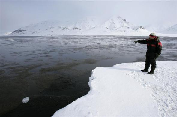 German Andreas Umbreit, who has lived for 21 years in the Norwegian Arctic town of Longyearbyen, points at open water in a fjord normally frozen solid, April 23, 2007.