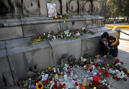 Denitsa Peicheva, 28, holds her son as she lays flowers next to candles left in memory of Bulgarian TV journalist Viktoria Marinova in Ruse, Bulgaria, October 9, 2018. REUTERS/Stoyan Nenov