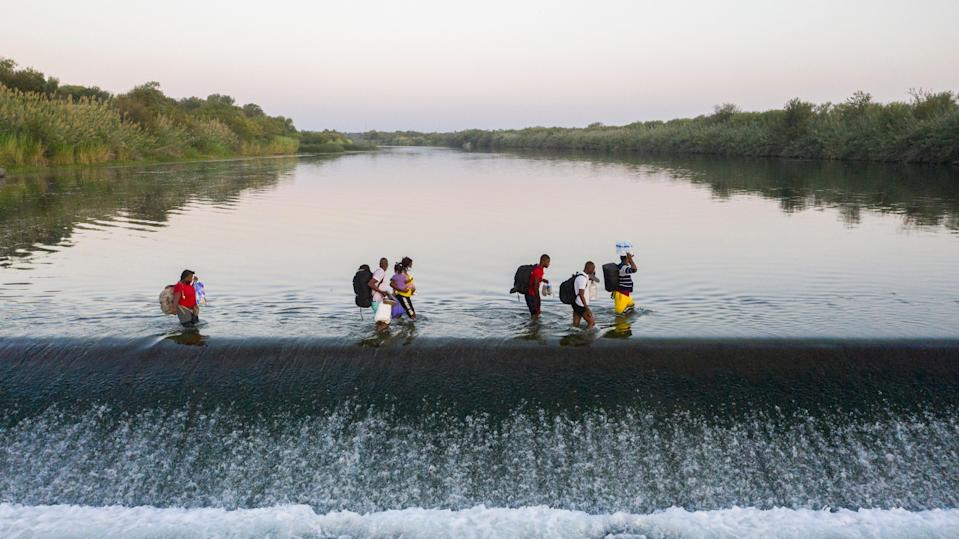 Haitian migrants cross the Rio Grande into Del Rio, Texas from Ciudad Acuna on Sept. 18, 2021. Thousands of migrants have arrived in the border city and have camped underneath the Del Rio International Bridge on the U.S. side of the border.