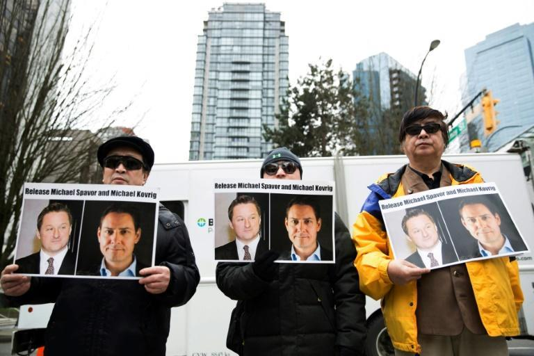 Protesters hold photos of Canadians Michael Spavor and Michael Kovrig, who are being detained by China