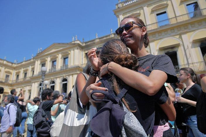 Students and researchers gathered to demonstrate outside the museum's still-smoldering remains (AFP Photo/Carl DE SOUZA)