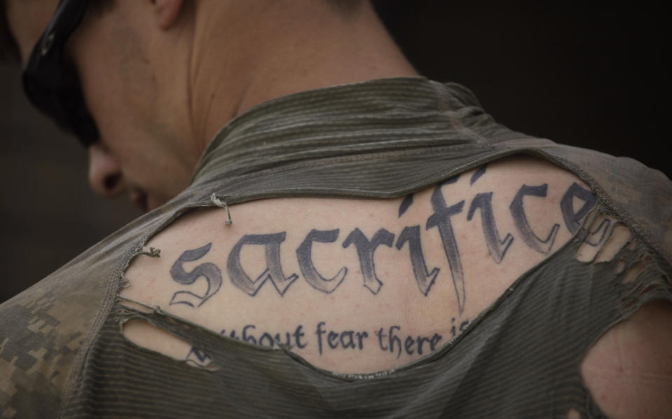 """A tattoo on the back of U.S. Army Sgt. James Wilkes of Rochester, N.Y., is seen through his torn shirt after a foot patrol with 1st Platoon, Charlie Company, 2nd Battalion, 1st Infantry Regiment, of the 5th Styker Brigade on May 8, 2010, in Afghanistan's Kandahar province. The full tattoo reads, """"Sacrifice. Without fear there is no courage."""" (AP Photo/Julie Jacobson, File)"""