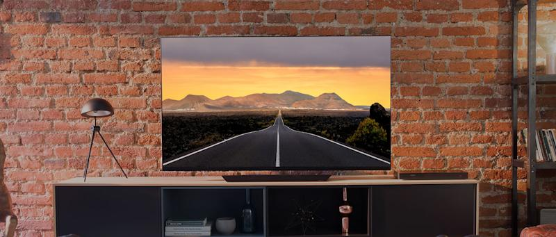 An LG OLED TV on an entertainment stand against a brick living room wall.