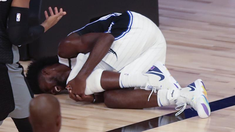 Jonathan Isaac holds his knee in pain on the floor.