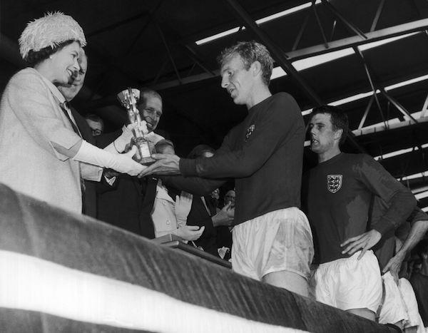 <p>Queen Elizabeth II presents the Jules Rimet trophy to the captain of the British team following England's world title win at the World Cup in Wembley. </p>
