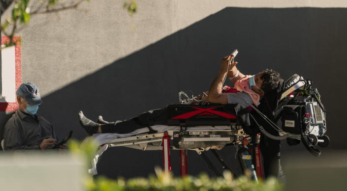 """An unidentified patient uses his mobile phone while receiving oxygen on a stretcher, as Los Angeles Fire Department Paramedics monitor him outside the Emergency entrance, waiting for his room at the CHA Hollywood Presbyterian Medical Center in Los Angeles Friday, Dec. 18, 2020. Increasingly desperate California hospitals are being """"crushed"""" by soaring coronavirus infections, with one Los Angeles emergency doctor predicting that rationing of care is imminent. (AP Photo/Damian Dovarganes)"""