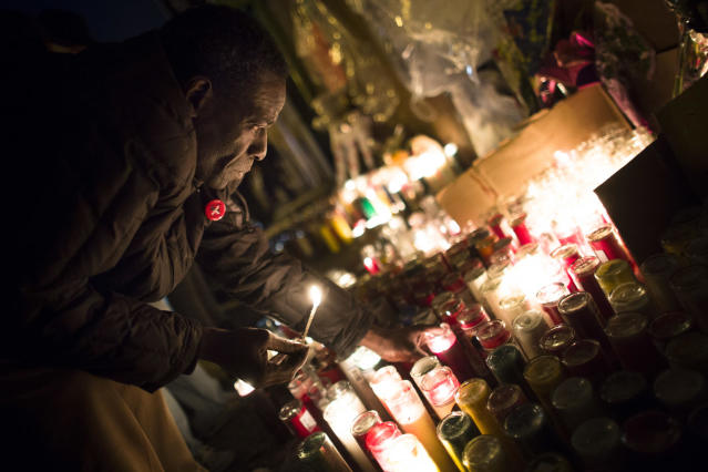 "Evan Brown, 53, lights candles during a vigil held for Kimani ""Kiki"" Gray in the East Flatbush neighborhood of Brooklyn, Wednesday, March 13, 2013, in New York. The 16-year-old was shot to death on a Brooklyn street last Saturday night by plainclothes police officers who claim the youth pointed a .38-caliber revolver at them. (AP Photo/John Minchillo)"