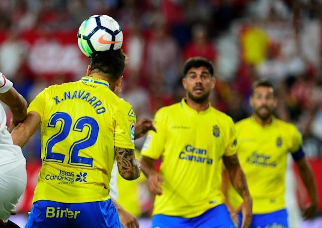 Las Palmas defender Ximo Navarro (L) heads the ball during the Spanish league match against Sevilla FC at the Ramon Sanchez Pizjuan stadium in Sevilla on September 20, 2017