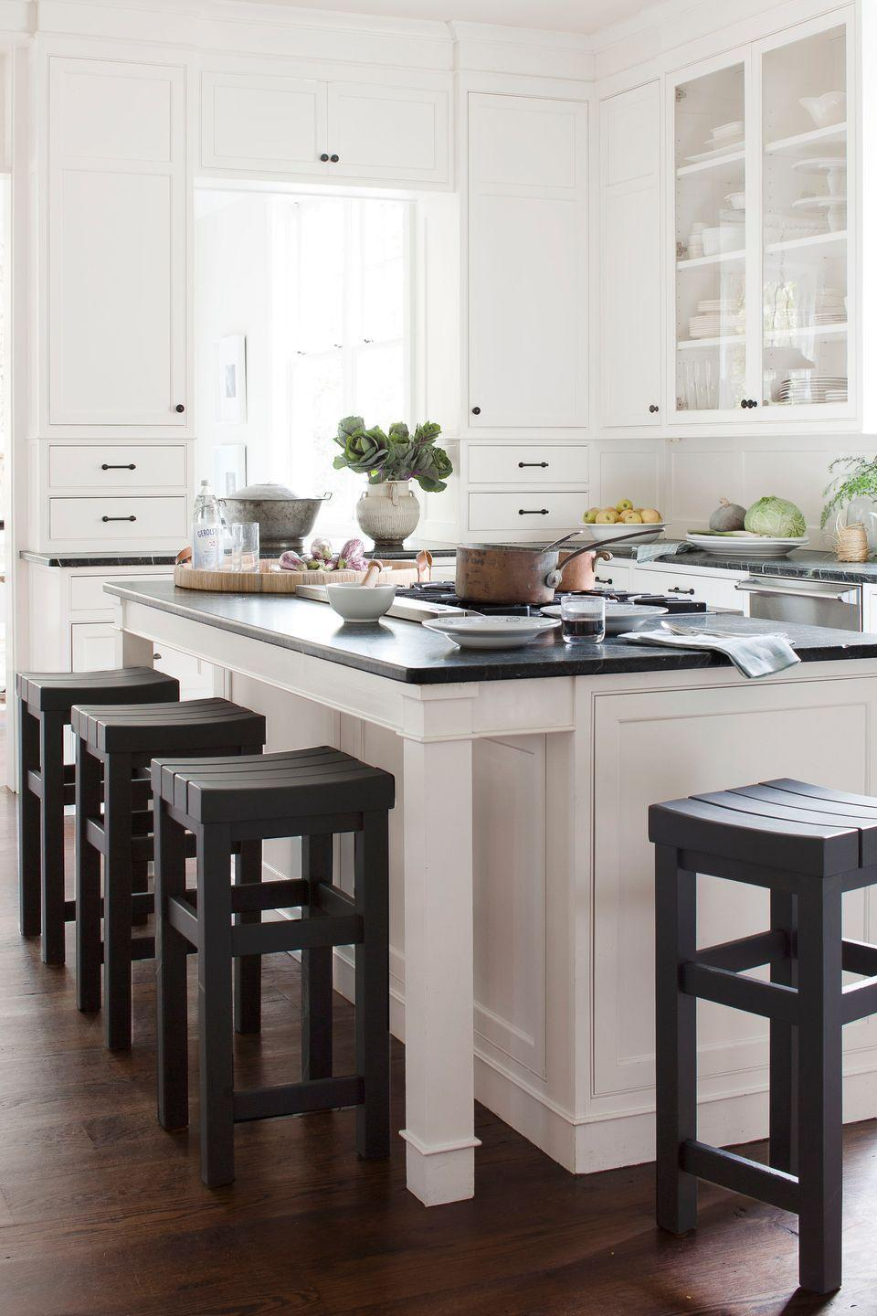 """<p>Dark-walnut floors, deep green soapstone counters, and custom stools (painted Benjamin Moore's Phelps Black) add balance and contrast to the kitchen's white cabinetry in this <a href=""""https://www.countryliving.com/home-design/house-tours/g1277/traditional-white-decorating-ideas/"""" rel=""""nofollow noopener"""" target=""""_blank"""" data-ylk=""""slk:Washington, D.C., home"""" class=""""link rapid-noclick-resp"""">Washington, D.C., home</a>. </p>"""