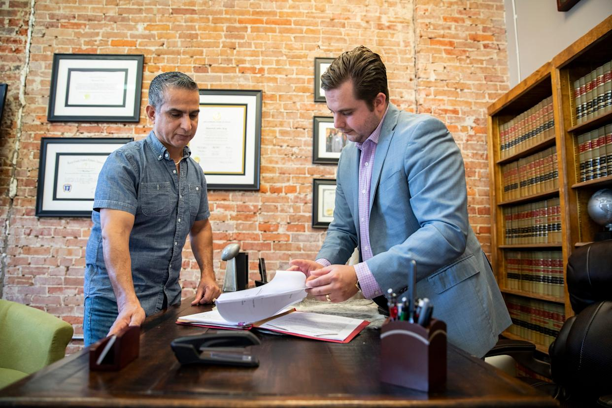 Revat Vara, left, who spent 11 years in prison for a wrongful DWI conviction, speaks with his lawyer Maverick Ray, right, in Houston. Vara studied the law in prison as he worked with his legal team to win his release in 2017.