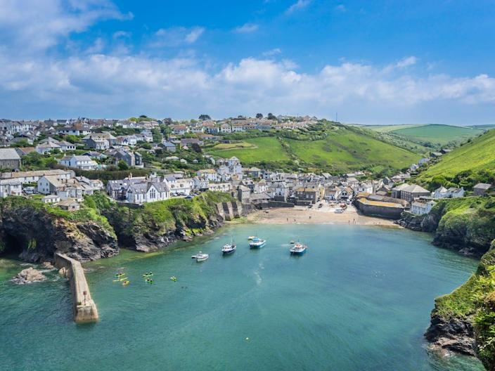 The Port of Issac in Cornwall UK with ocean and rocky cliff-sides.