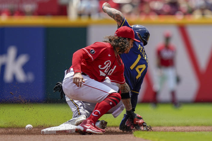 Milwaukee Brewers' Jace Peterson (14) slides safely into second base ahead of the tag from Cincinnati Reds second baseman Jonathan India during the first inning of a baseball game in Cincinnati, Sunday, July 18, 2021. (AP Photo/Bryan Woolston)
