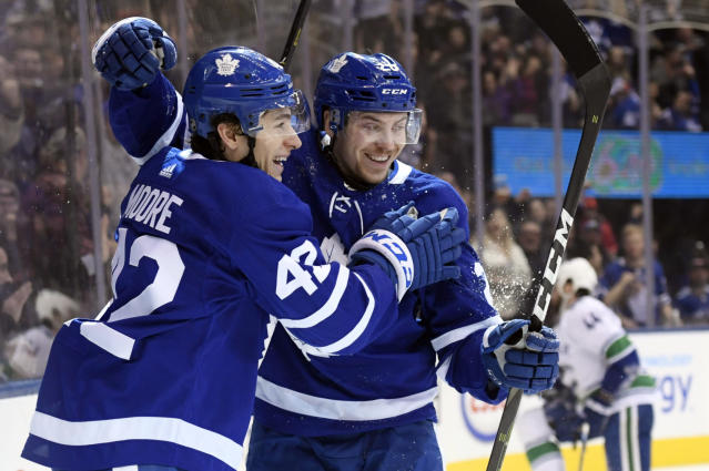 Toronto Maple Leafs' Trevor Moore (42) celebrates his first NHL goal with teammate center Par Lindholm (26) during the first period of an NHL hockey game against the Vancouver Canucks, Saturday, Jan. 5, 2019, in Toronto. (Nathan Denette/The Canadian Press via AP)