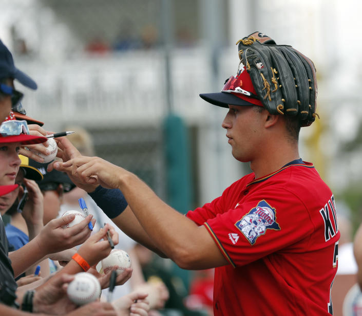FILE - Minnesota Twins right fielder Alex Kirilloff signs autographs before the start of a spring training baseball game against the Baltimore Orioles in Fort Myers, Fla., in this Monday, March 4, 2019, file photo. Alex Kirilloff has never played in a regular season major league game, but he is on track to become Minnesota's regular left fielder. (AP Photo/John Bazemore, File)