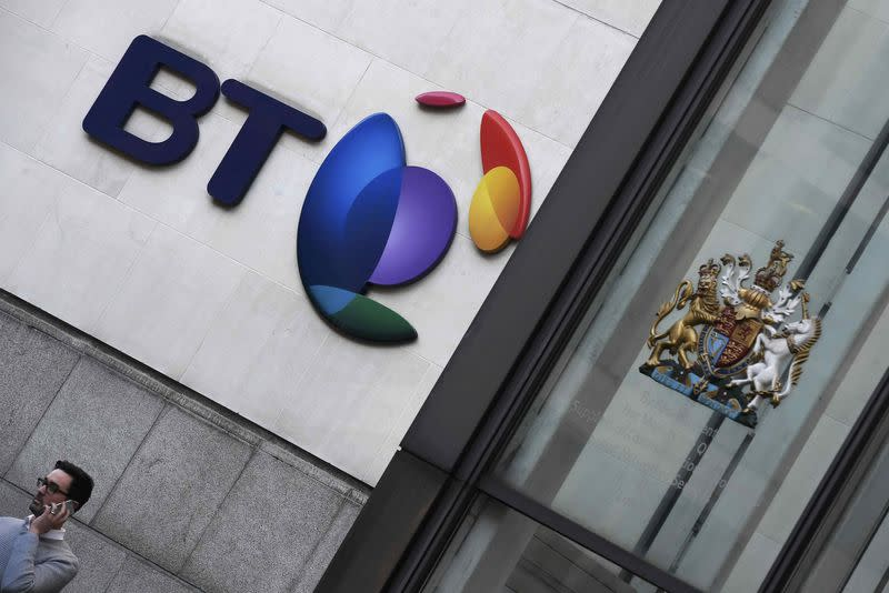 A man speaks on a mobile phone underneath a BT logo outside of offices in the City of London