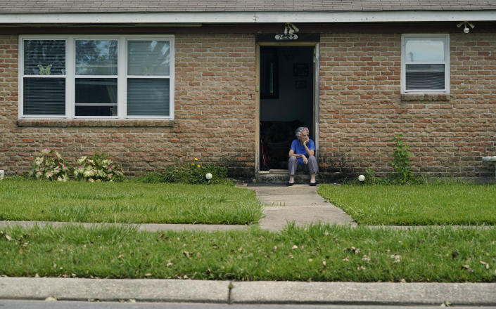 Berth Topolanek, center, who lost power due to Hurricane Ida, watches from her doorstep as energy workers assess and repair lines in her neighborhood, Wednesday, Sept. 1, 2021, in New Orleans, La. Power was restored to an area just blocks away Monday, but some part of New Orleans may be without power for weeks. (AP Photo/Eric Gay)