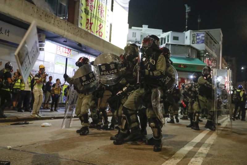 Riot police clash with protesters on the street of Yuen Long, Hong Kong, Monday, Oct. 21, 2019. A evening sit-in at a suburban train station on the three-month anniversary of a violent attack there on protesters by men with suspected organized crime ties. (AP Photo/Mark Schiefelbein)