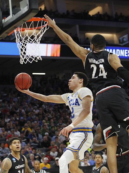 UCLA guard Lonzo Ball, left, goes to the basket against Cincinnati forward Kyle Washington during the first half of a second-round game of the NCAA men's college basketball tournament in Sacramento, Calif., Sunday, March 19, 2017. (AP Photo/Steve Yeater)