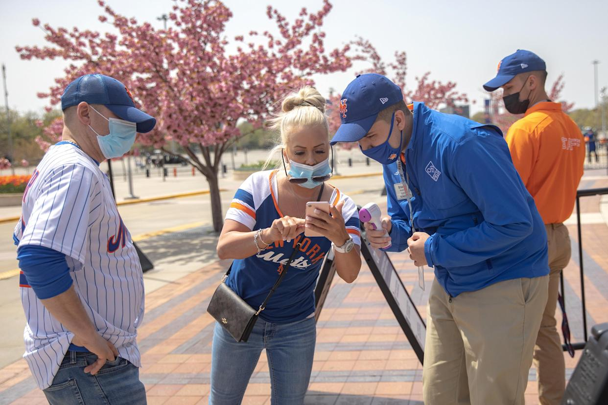 A Mets fan shows a vaccine passport on her phone as she arrives for a game at Citi Field in New York on April 24. (Jeenah Moon/Reuters)