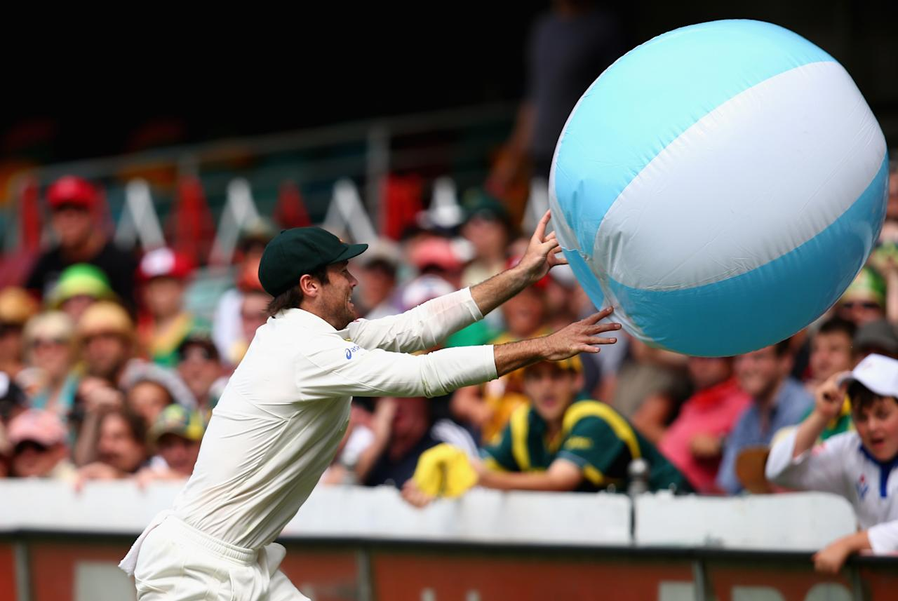 BRISBANE, AUSTRALIA - NOVEMBER 11: Rob Quiney of Australia throws a beach ball back into the crowd during day three of the First Test match between Australia and South Africa at The Gabba on November 11, 2012 in Brisbane, Australia.  (Photo by Ryan Pierse/Getty Images)