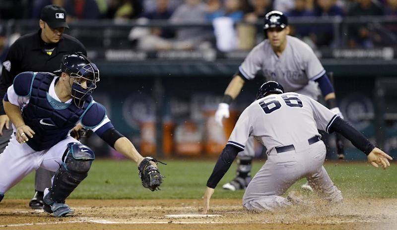 New York Yankees ' John Ryan Murphy (66) touches home plate ahead of a tag attempt by Seattle Mariners catcher Mike Zunino, left, to score on a single hit by Yankees' Derek Jeter in the fourth inning of a baseball game, Thursday, June 12, 2014 in Seattle. (AP Photo/Ted S. Warren)