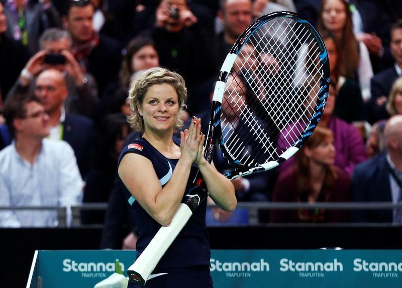 FILE PHOTO: Belgium's Clijsters applauds after receiving a giant racket during an exhibition tennis match marking the end of her professional career in Antwerp