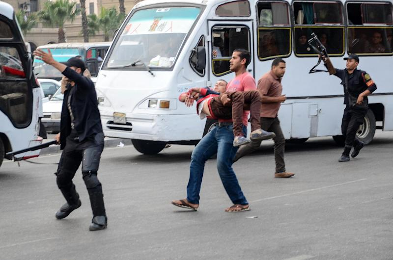 An Egyptian policeman in plain clothes is evacuated after he was injured during a bomb explosion outside the main gate of Cairo University on October 22, 2014 (AFP Photo/Mahmud Hasan)